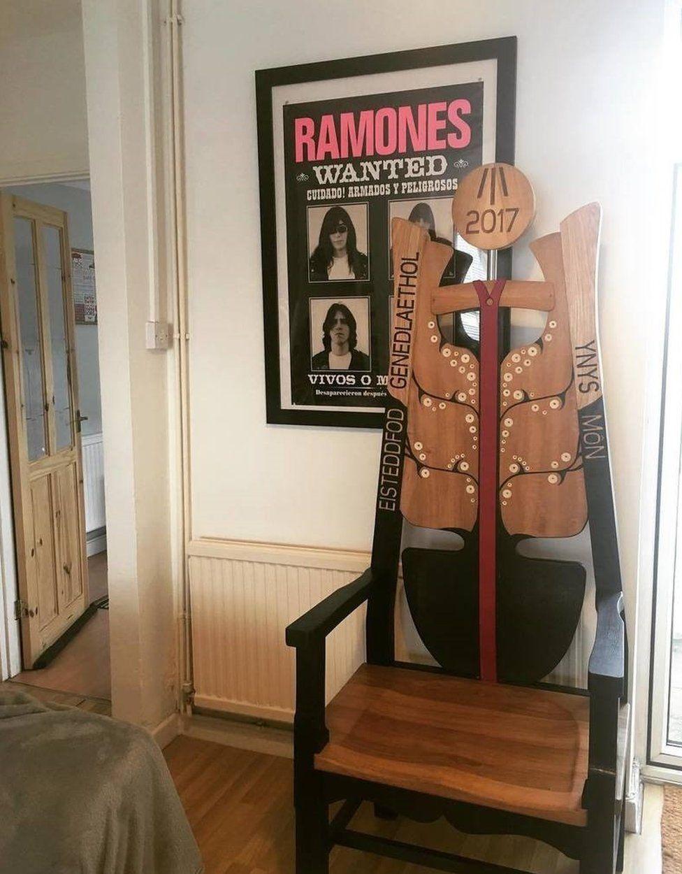 Cadair Eisteddfod Sir Fôn eleini yn ei chartref newydd, o dan poster y Ramones