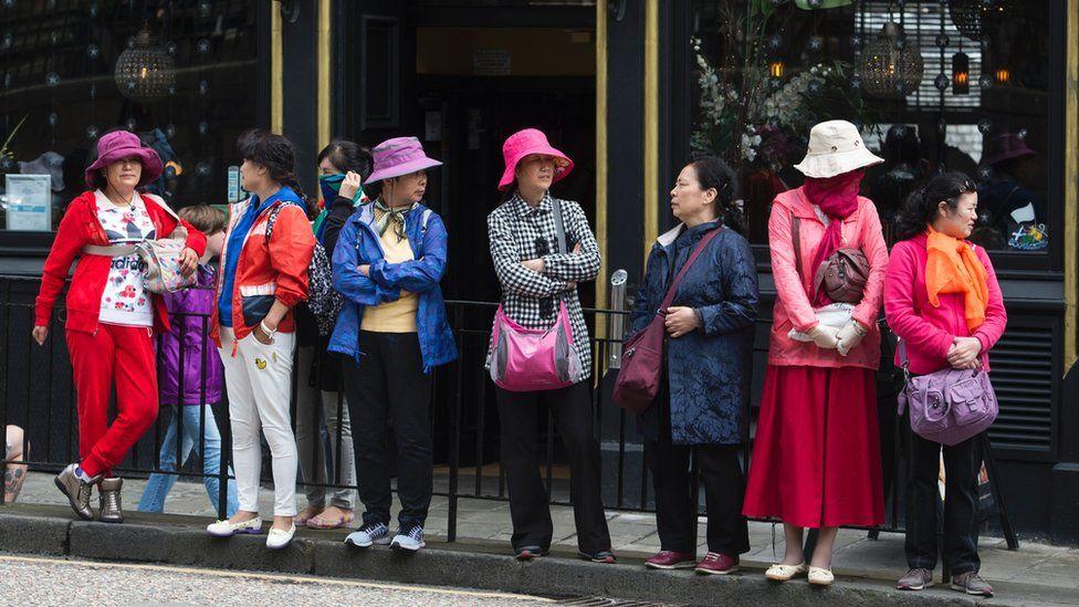 Tourists stand outside a pub in Edinburgh