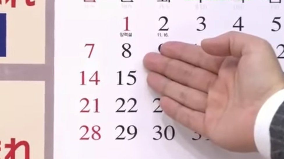 A TV presenter points to 8 January on a North Korean calendar