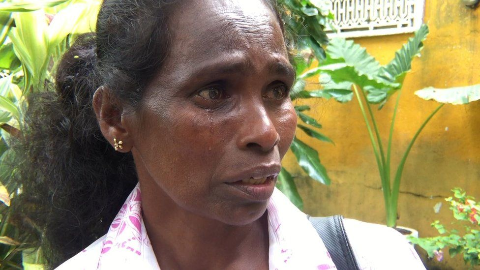 A woman being interviewed is pictured crying