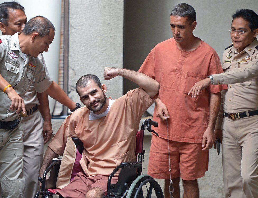 Saeid Moradi, 29, (C), an Iranian suspected of involvement in the February 2012 bomb blasts in Bangkok, gestures to the media next to Mohammad Khazaei (2nd R), 43, during an apprearance at the southern criminal court in Bangkok on August 22, 2013.