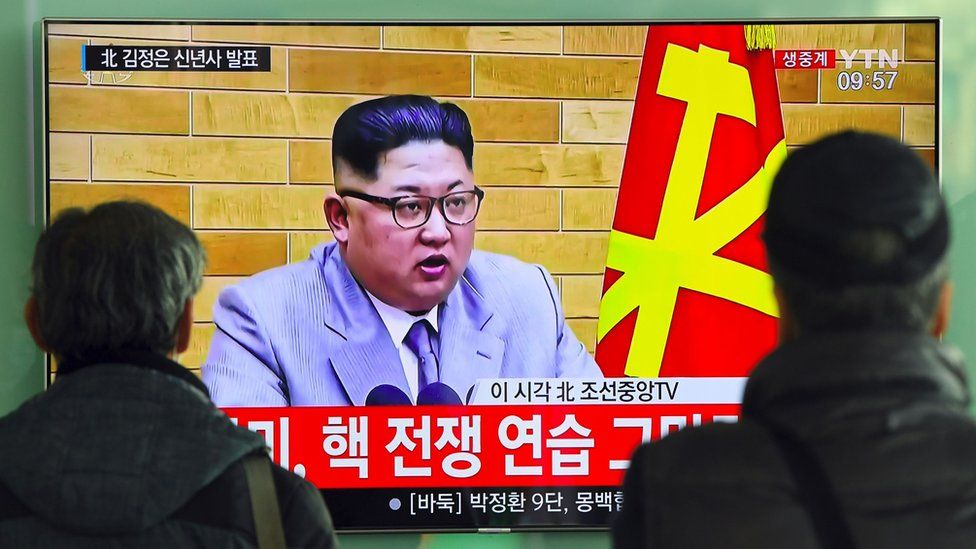 """People watch a television news broadcast showing North Korean leader Kim Jong-Un""""s New Year""""s speech, at a railway station in Seoul on January 1, 2018."""