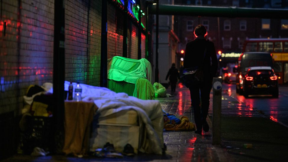 A commuter walks past the shelters and tents of homeless people underneath a railway track in London on 1 February