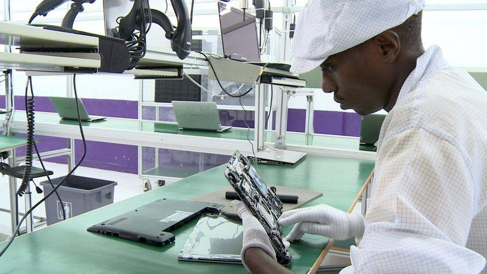 factory worker assembles computer