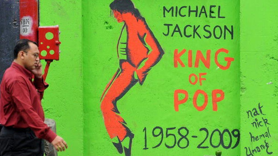 """An Indian pedestrian speaks into a cellular telephone as he walks past a grafitti image of the late """"King of Pop"""" Michael Jackson on a wall in Mumbai on August 28, 2009,"""
