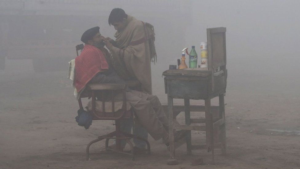A Pakistani barber shaves a customer alongside a road amid heavy fog and smog conditions in Lahore on January 24, 2019.