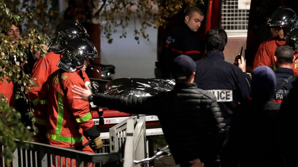 Police officials and rescue personnel transport the body of a tiger which had escaped from a circus into a vehicle in Paris on November 24, 2017,