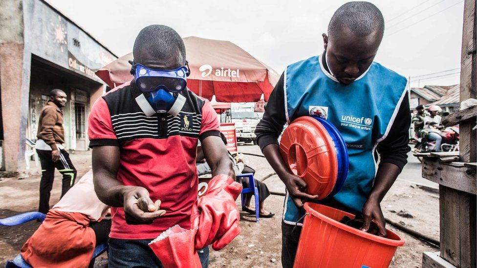 Health workers wear protective gear to mix water and chlorine in Goma