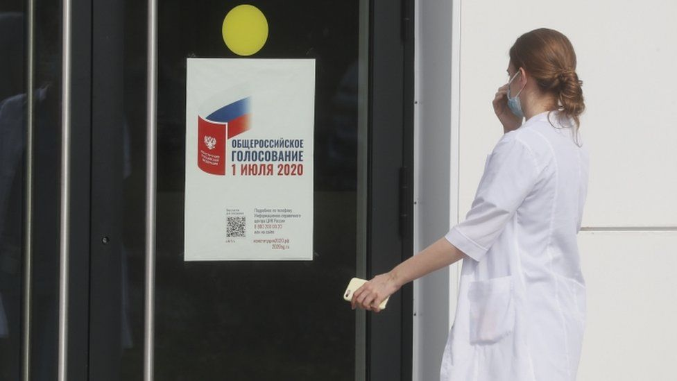 A medical specialist approaches the front door of a hospital complex with a pasted poster