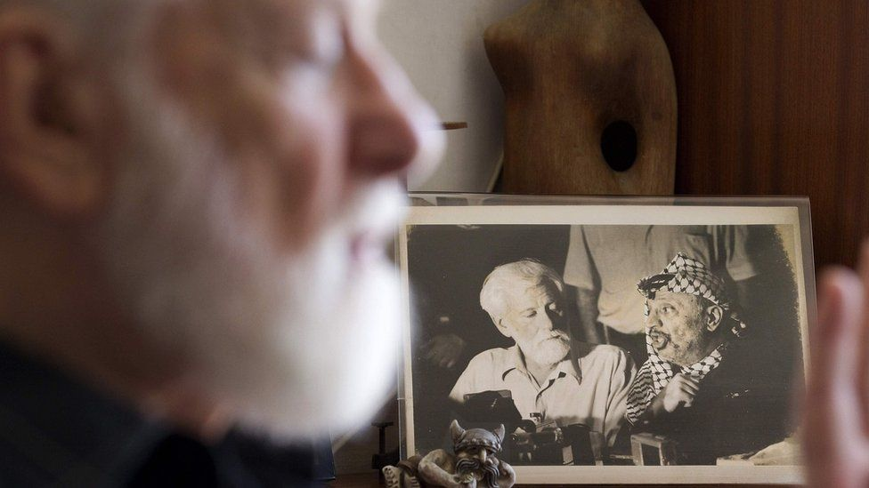 File photo taken on 26 July 2011 showing Uri Avnery speaking next to a photograph of him meeting the late Palestinian leader Yasser Arafat in Beirut in 1982