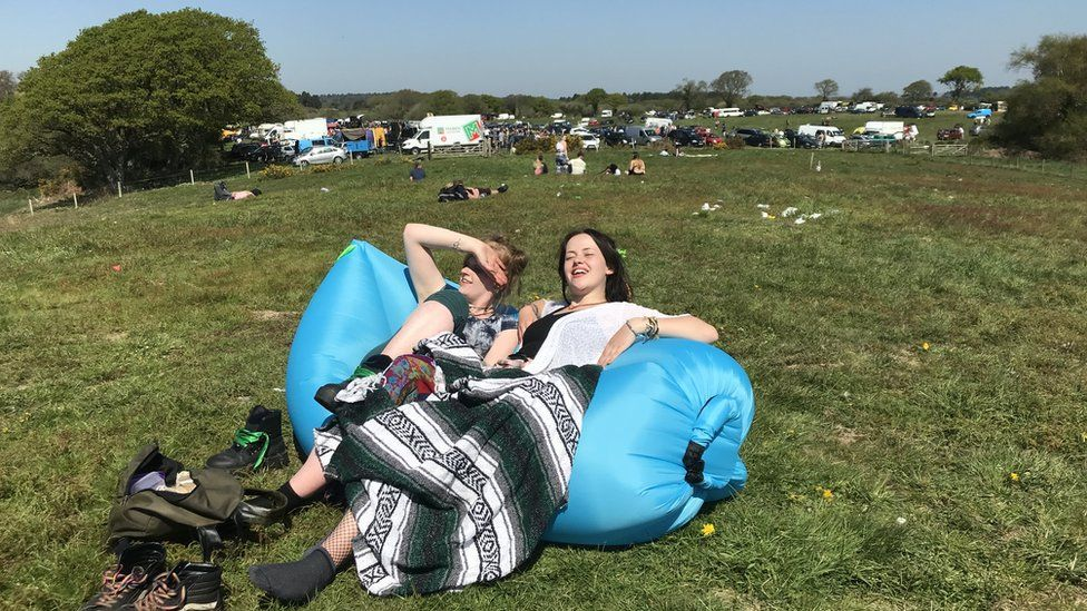 Revellers at the rave near Corfe Castle relaxing in the sunshine