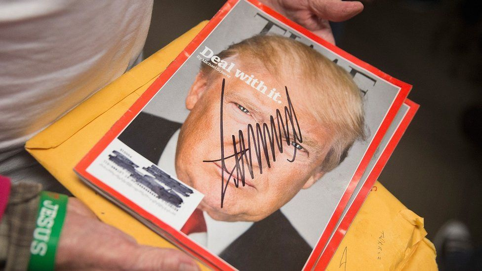 A woman holds an copy of Time magazine that Donald Trump has signed.