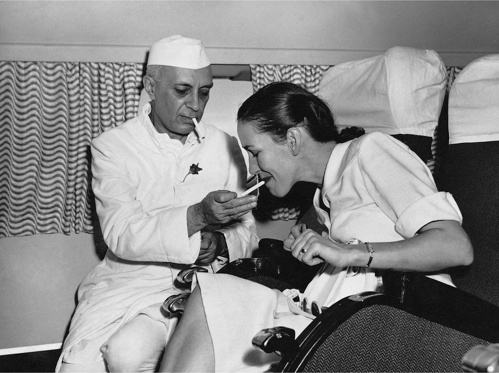 Mr Nehru lights a cigarette for the wife of a British diplomat while on board the first BOAC or round-the-world flight in India.
