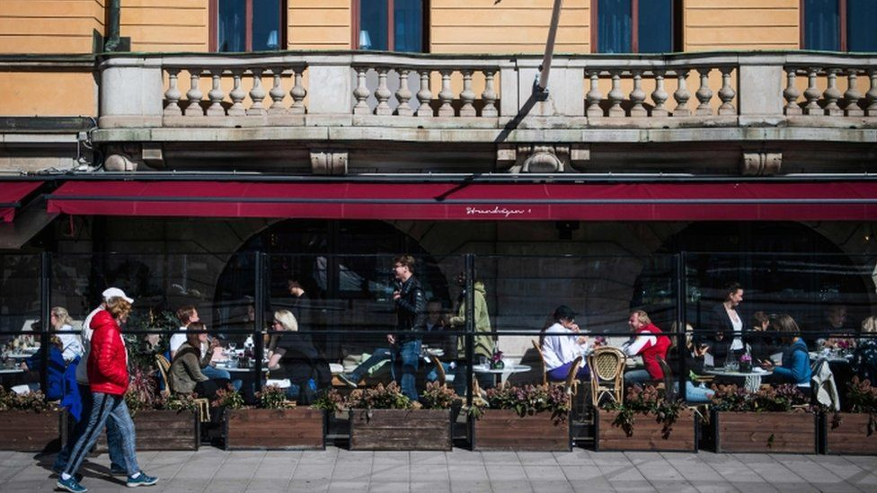 People enjoy the spring weather as they sit at a restaurant in Stockholm on April 15, 2020,