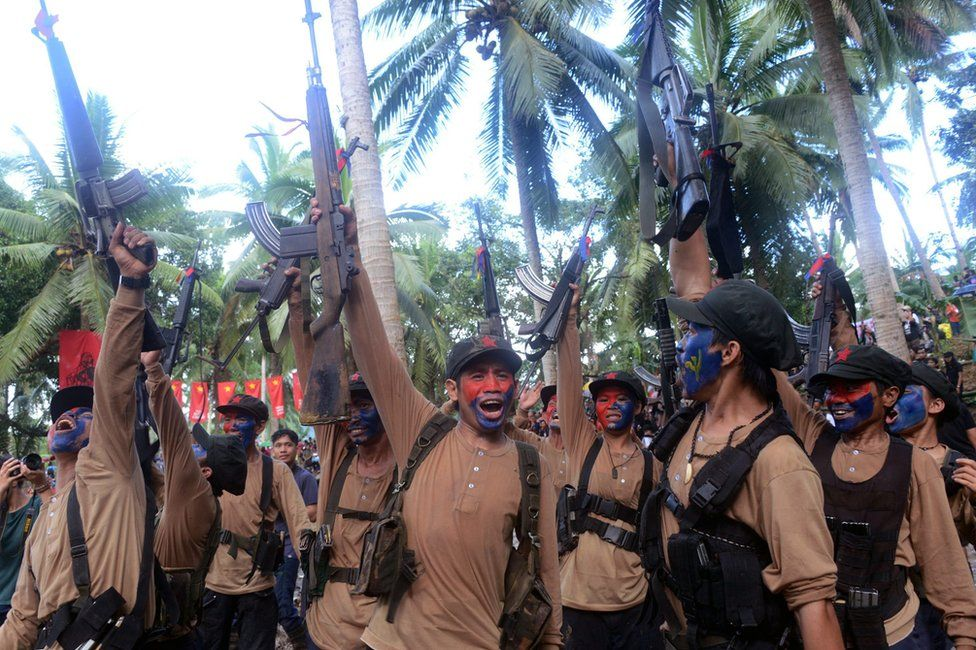 A picture made available on 29 December 2016 shows members of the NPA waving their guns during their anniversary celebration in the mountains of Sierra Madre, Quezon province, Philippines.