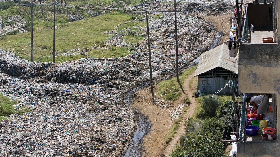 A woman washes her clothes near a rubbish dump in Nairobi, Kenya.
