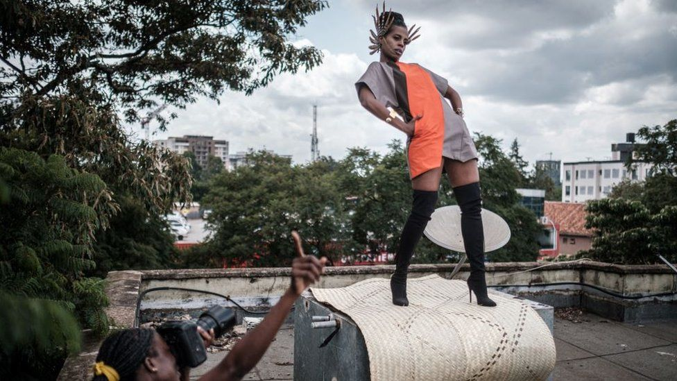 Kenyan photographer and art director Barbara Minishi (L) takes pictures of her room mate and fashion stylist Wambui Thimba (R)