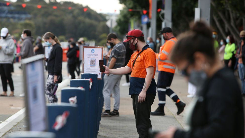 Las colas de personas usan un código QR para registrarse en un estadio de Sydney para su cita de vacunación