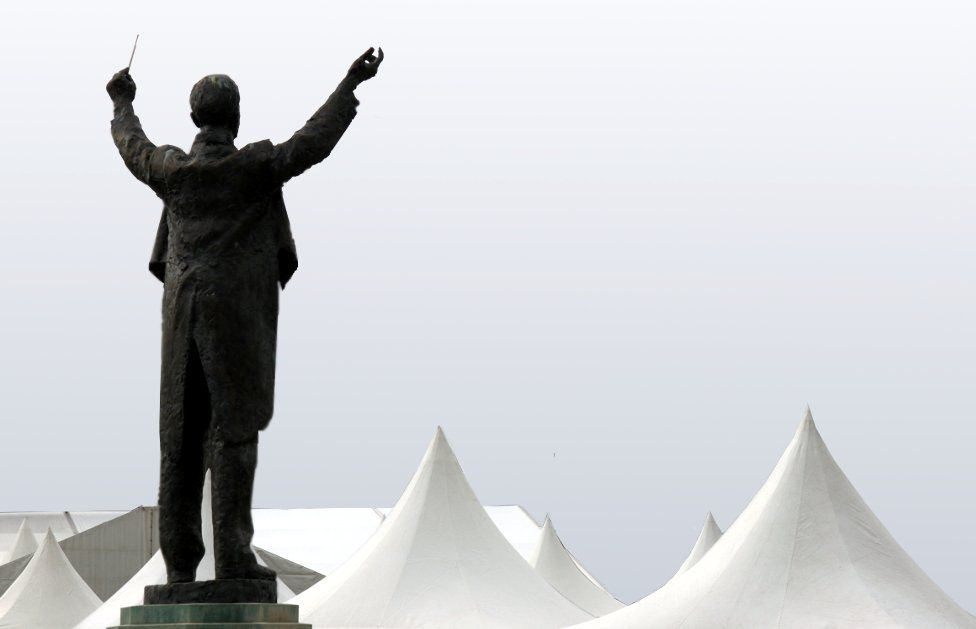 A statue in front of tents