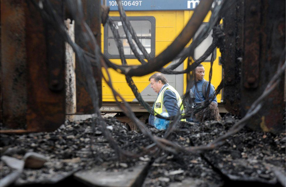 Workers walking along the track next to burnt-out trains are seen through a gap in the wreckage