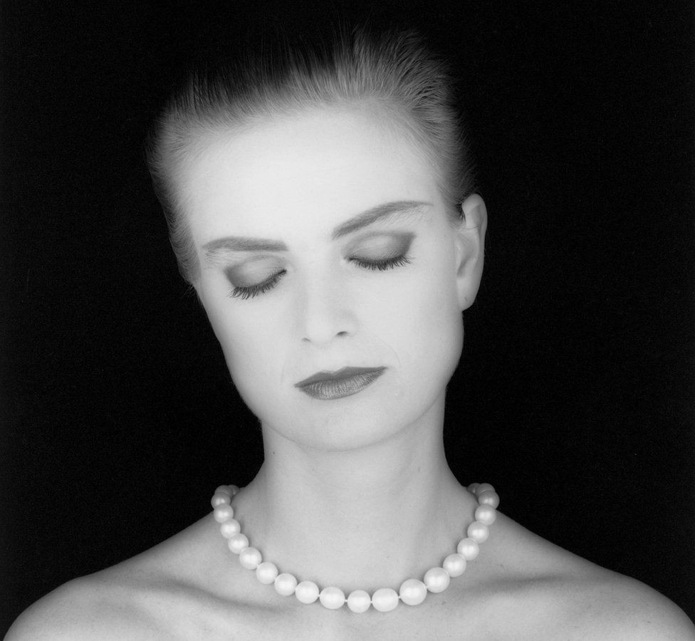 Princess Gloria von Thurn and Taxis wears a pearl necklace as she poses with her eyes closed