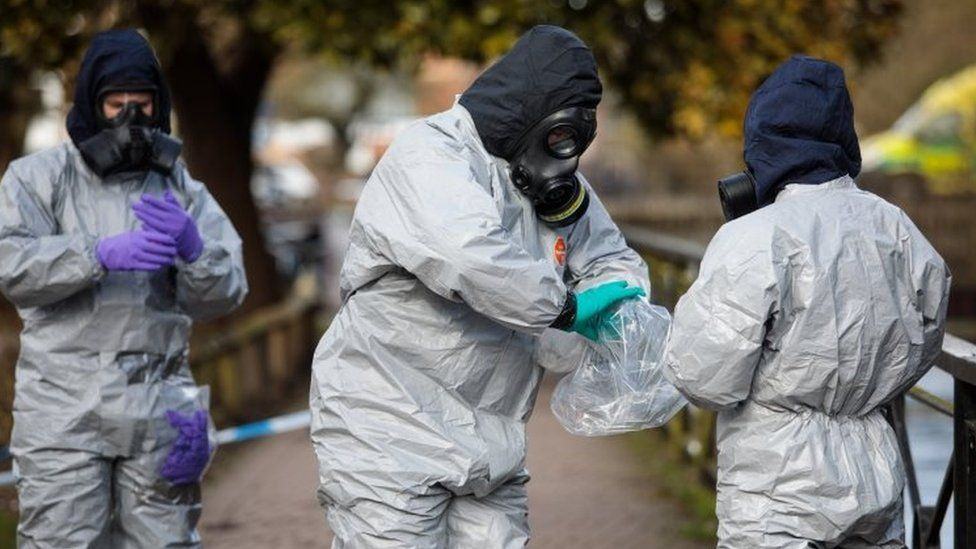 Police officers in protective suits and masks work near the scene