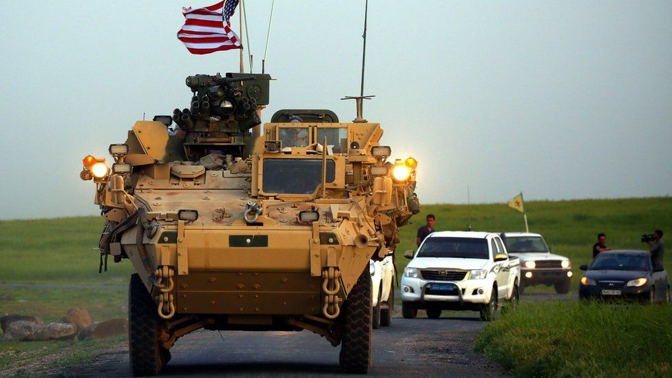 US forces, accompanied by YPG fighters, drive an armoured vehicle in northern Syria (19 December 2018)