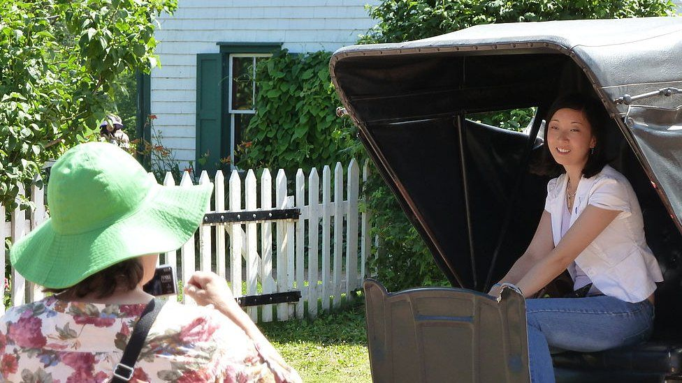 A Japanese tourist takes a photo outside the real Green Gables house in Canada in 2011.