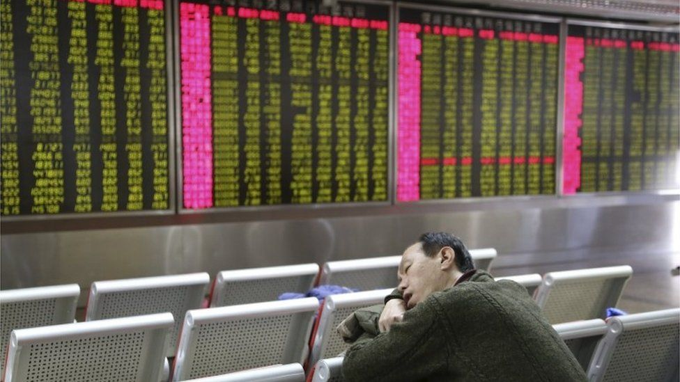 An investor takes a nap in front of an electronic board showing stock information at a brokerage house in Beijing