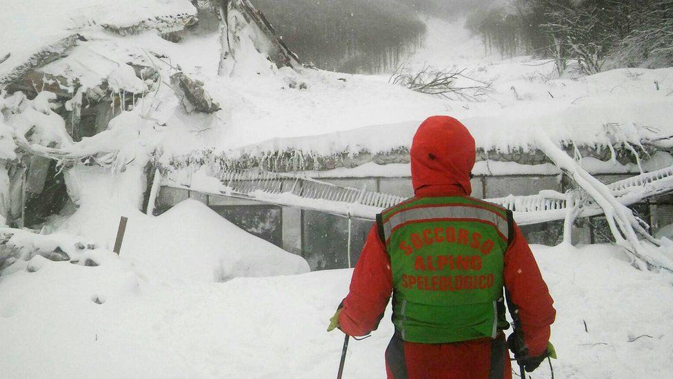 A rescuer looks at the ruins of the Rigopiano hotel, 19 january