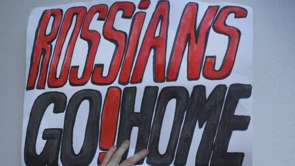 A demonstrator holds a placard during an opposition rally in Minsk against the deployment of Russian military bases in Belarus (04 October 2015)