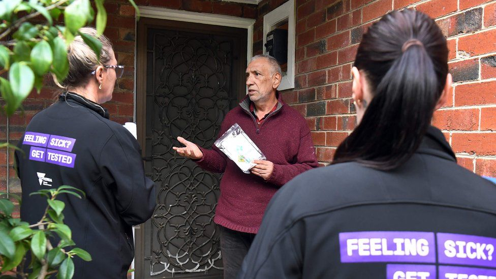 Health workers speak to a resident in an affected Melbourne area