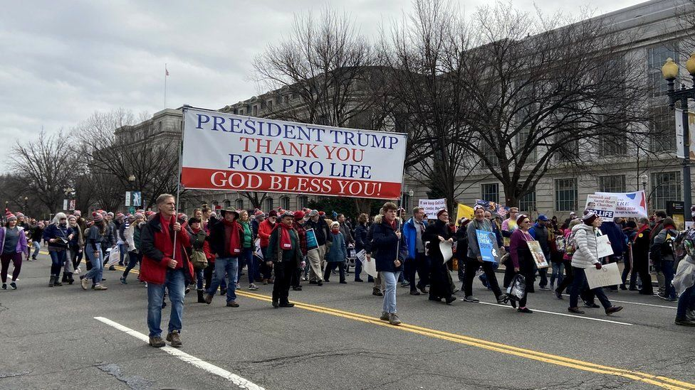 Marchers hold a sign saying president Trump, thank you for pro-life, god bless you