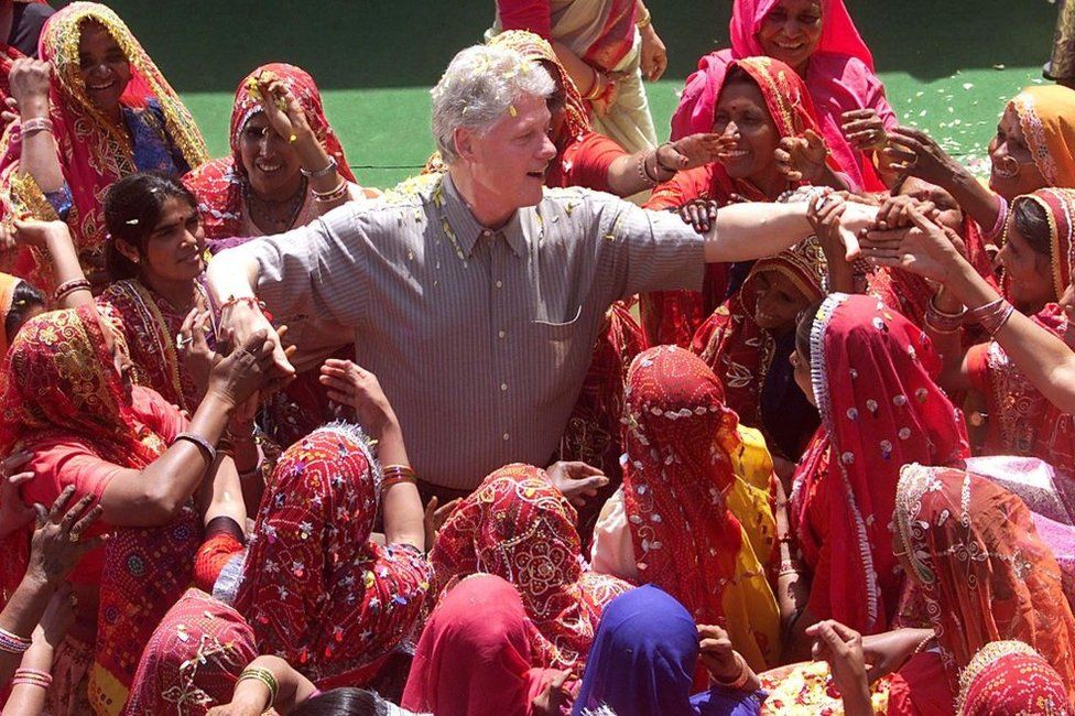 US President Bill Clinton shakes hands with local villagers after touring Nayla Village 23 March 2000.