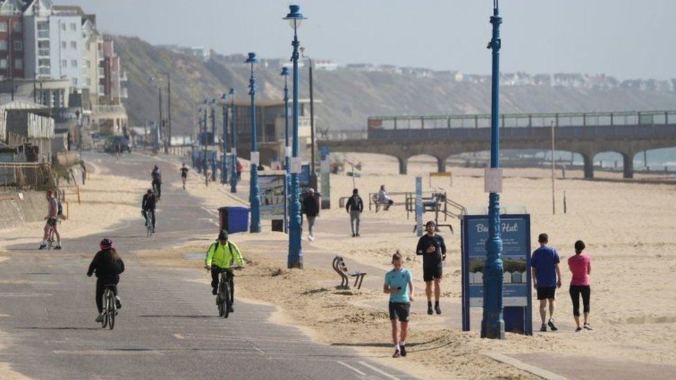 People exercise along the seafront on Boscombe Beach