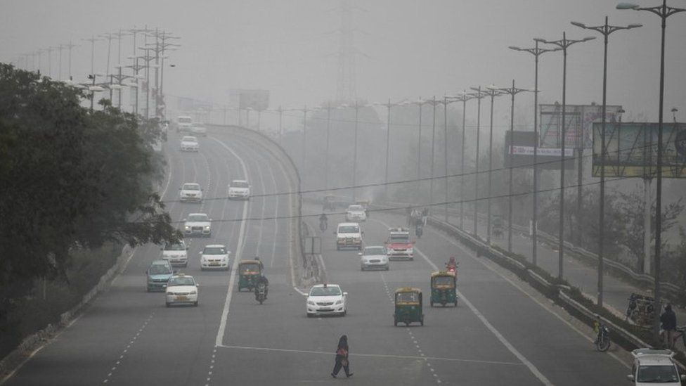 An Indian woman crosses a road as vehicles move through morning smog on the last day of a two-week experiment to reduce the number of cars to fight pollution in New Delhi, India, Friday, Jan. 15, 2016