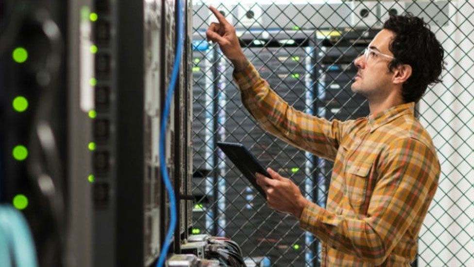 Man examining a server rack