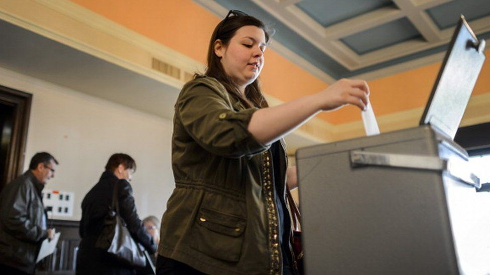 A woman casts her ballot in Switzerland