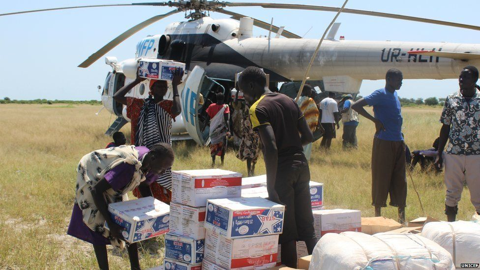 Women collect food supplies from a United Nations helicopter