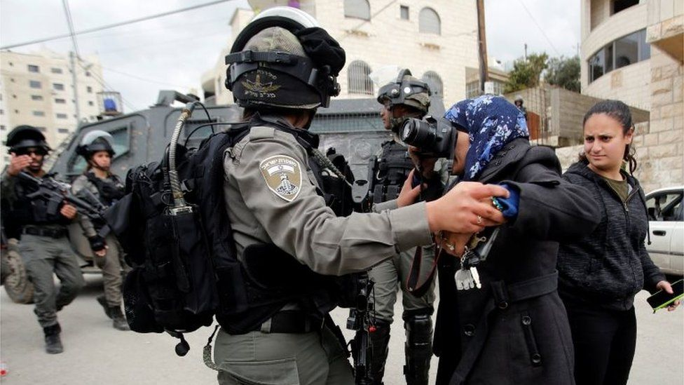 A local photographer takes pictures as an Israeli border police member holds her back during the demolition of a Palestinian house whose owners said they were informed by the Israeli forces that they didn't obtain a construction license, in Beit Jala in the Israeli-occupied West Bank on 2 April 2019.