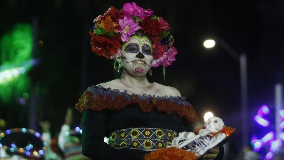 A woman dressed as a Mexican catrina poses for a photo in Medellín