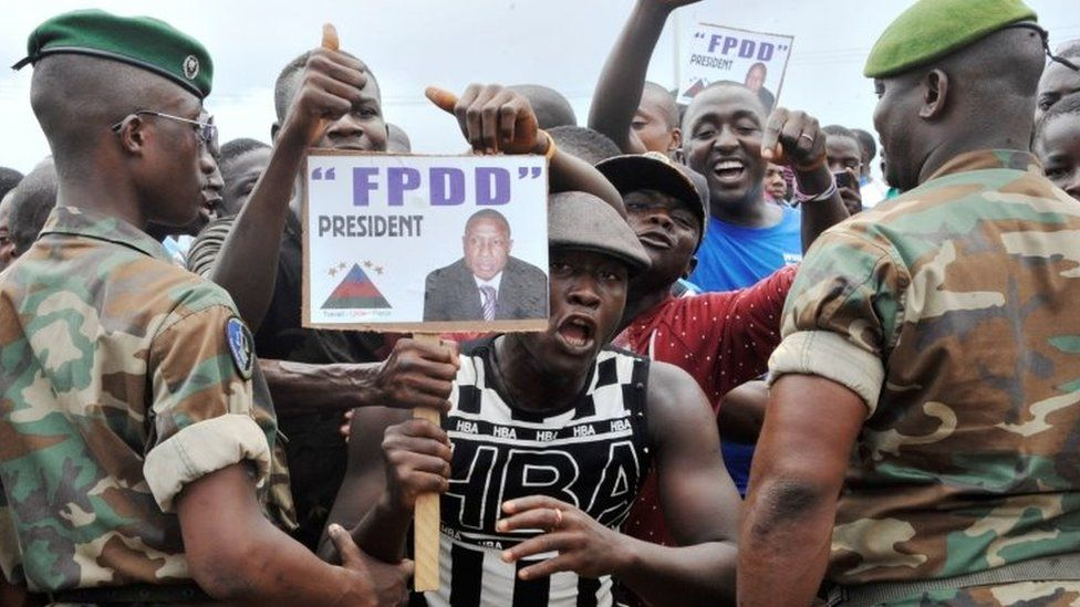 Supporters of Guinea's exiled former junta chief Moussa Dadis Camara demonstrate in front of soldiers, on 26 August 2015 at the airport in Conakry