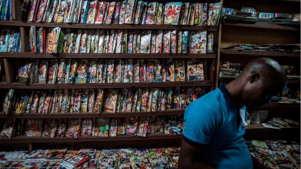 A man stands in a shop selling Nollywood films
