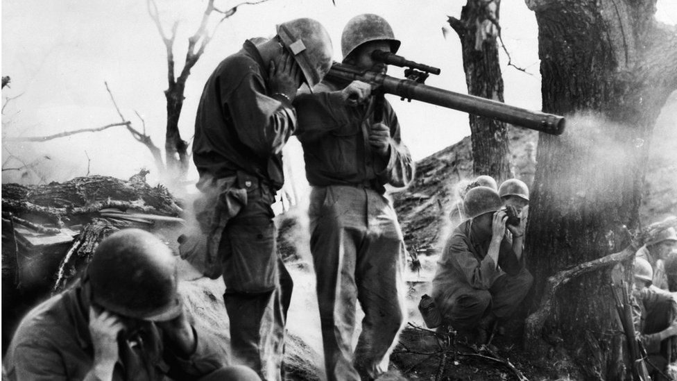 US infantrymen cover their ears as one fires a 75mm recoilless rifle, at the front lines in Korea.