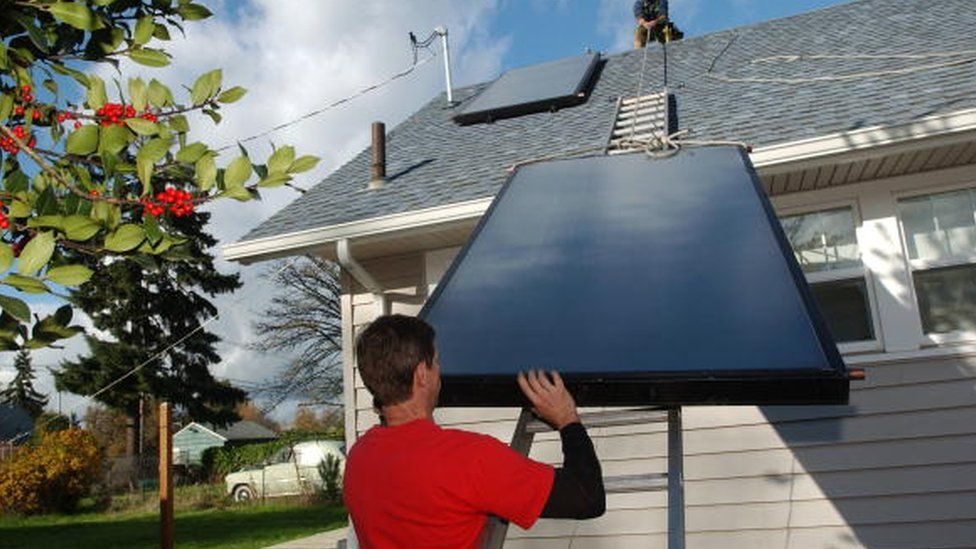 A man installs solar panels for a domestic hot water system in the US