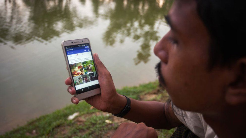 A Rohingya ethnic minority man looking at Facebook on his cell phone