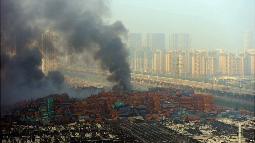 Fire and smoke rise at the site of the massive explosions in Tianjin on 13 August 2015