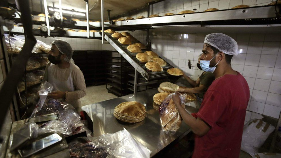 """Bakers package workers package freshly-produced bread coming off a production line at an automated bakery in Lebanon""""s capital Beirut (1 July 2020)"""
