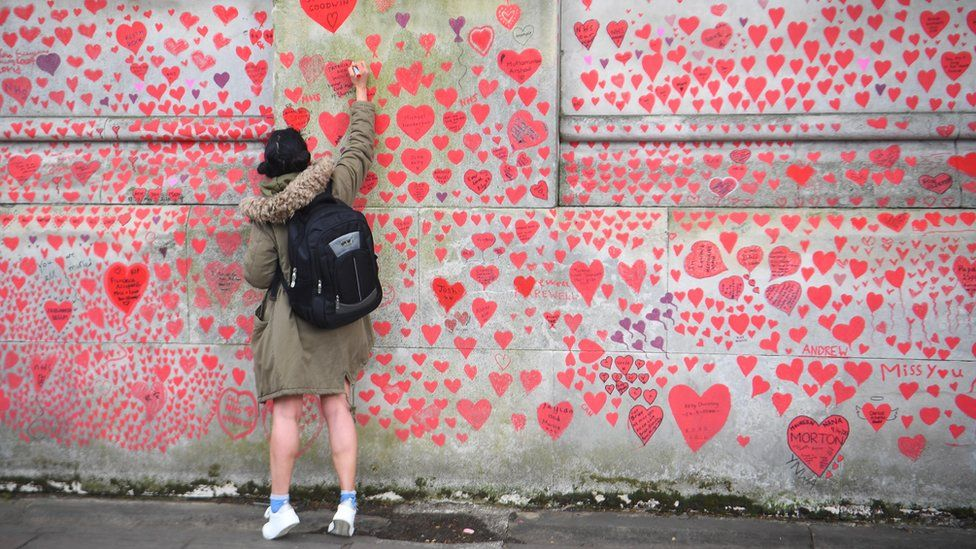 A person writes in a heart on the National Covid Memorial Wall on the Embankment in London