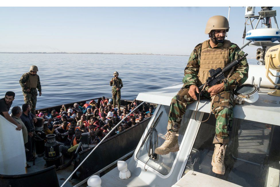 A Libyan coast guardsman watches over an operation to rescue illegal immigrants attempting to reach Europe